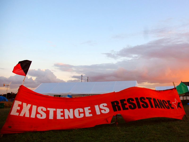 'Existence is Resistance!' Banner at the Climate Camp in Sipson village, wjhich wold be entirely destroyed by a third Heathrow runway, 16th August 2007. Photo: Alice via Flickr (CC BY-NC-ND).