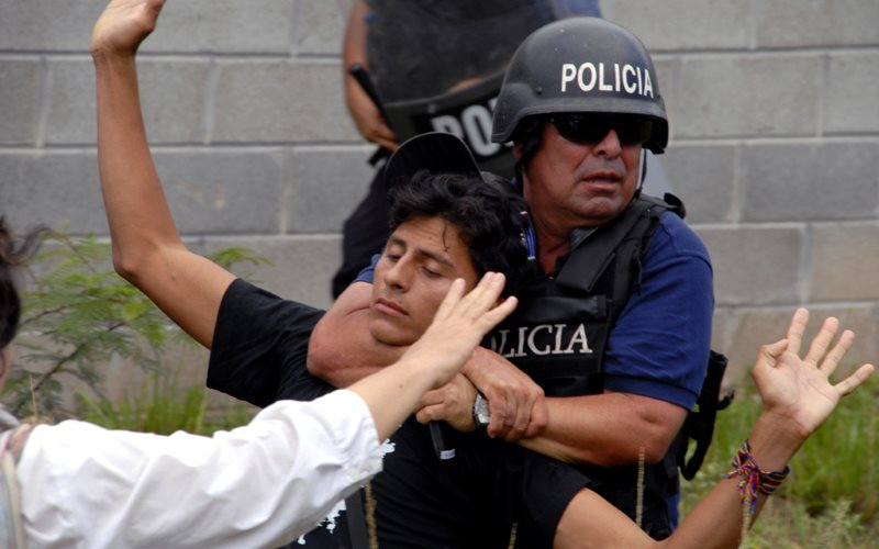 A COPINH protestor with Honduran policeman. Photo: Felipe Canova via Flickr (CC BY-NC).
