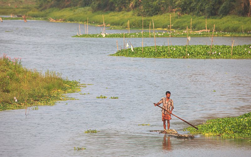 A local fisherman navigates the Diphlu River, which runs alongside India's Kaziranga national park - which operates a strict 'shoot on sight' policy for people found within the park boundaries. Photo: Frank Boyd via Flickr (CC BY-NC-SA).