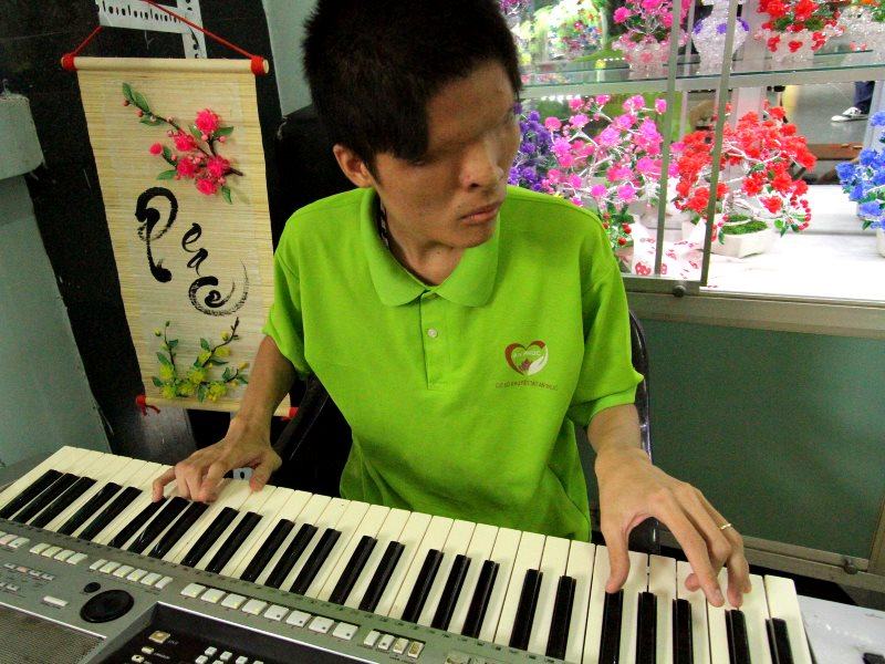 A keyboard player, blind from birth due to a genetic defect induced by Agent Orange, performing at the War Remnants Museum. Photo: Mick Grant.