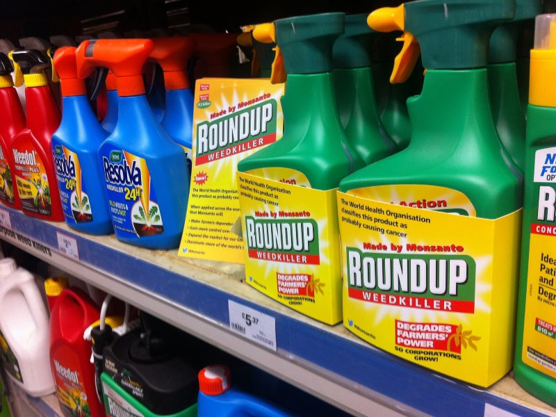 Bottles of Monsanto's Roundup weedkiller relabeled by Global Justice Now activists, April 2016. Roundup contains glyphosate, a chemical that the WHO classifies as 'probably carcinogenic'. Photo: Global Justice Now via Flickr (CC BY).