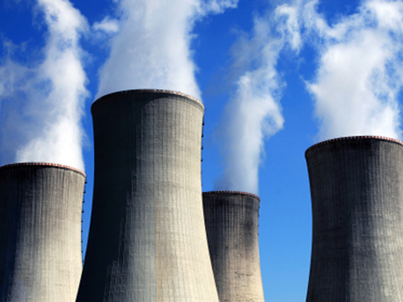 Smoke rises from a nuclear facility's four chimneys