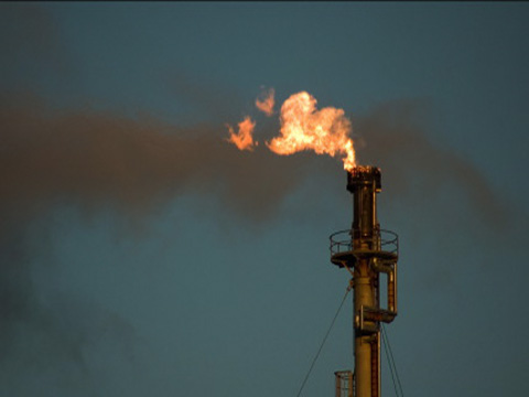 A flare burns waste gas at an oil refinery
