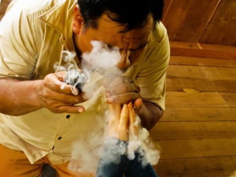 A maestro using tobacco smoke during healing. Photo: The Temple of the Way of Light.