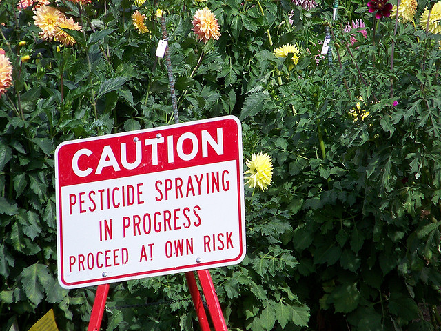 Caution - pesticide spraying in progress - proceed at own risk. Sign in Manito Park, Spokane, WA. Photo:  jetsandzeppelins via Flickr.com.