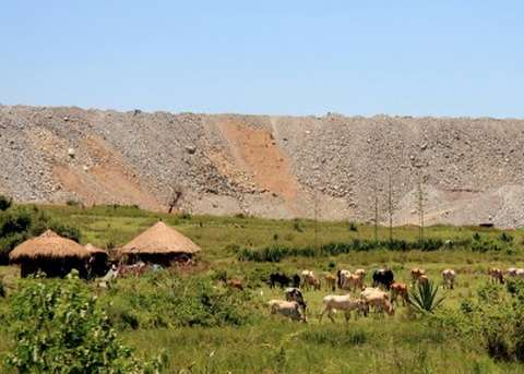 The spoil heap of Barrick's North Mara open pit gold mine rises above the pastoral landscape around Nyamongo village, Tanzania. Photo: Plenty's Paradox via Flickr.