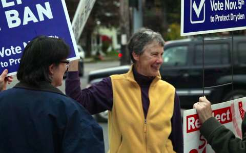 Marie McRae and the Cippolla-Dennis' smile in streets as they hold signs in support of the Dryden fracking ban. Photo: Chris Jordon-Bloch / Earthjustice.