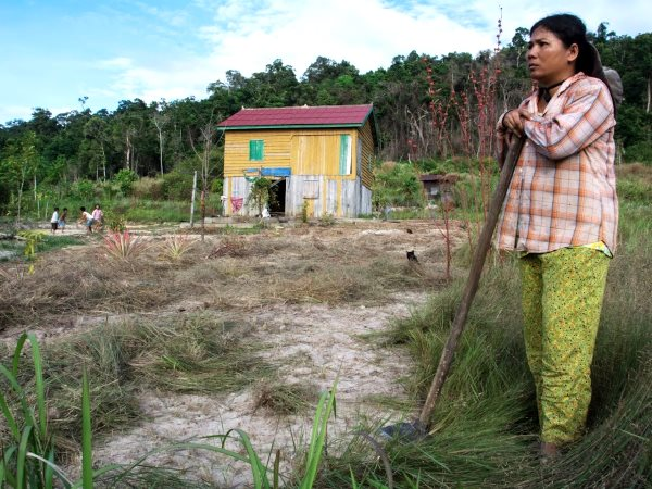 Mrs Sok Lim is toiling with a hoe to clear the course grasses that cover her small plot. One of dozens of houses strung along the dusty road comprising Phny Meas village in Botum Sakor National Park, Cambodia. Photo: Rod Harbinson.