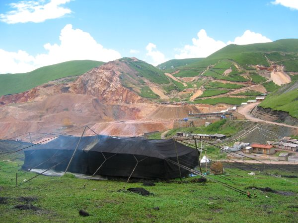 A Tibetan nomad tent stands before a mountainside being ripped apart by mining.