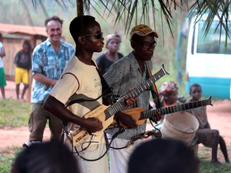 Martin Cradick playing guitar with Baka musicians Ndeke and Mbeh. Photo: Baka Beyond.