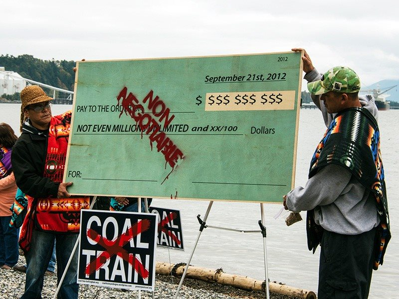 Lummi members hold a symbolic check burning protest to demonstrate that no amount of money can buy their support. Photo: Paul Anderson / EarthJustice.
