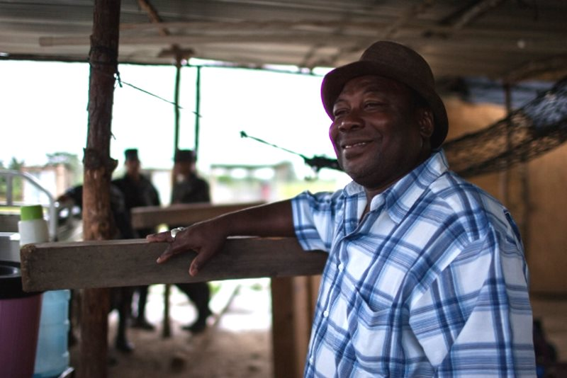 A resident of Vallecito accompany's singers as they preform traditional Garifuna songs. Photo: Jeff Abbott / WNV.
