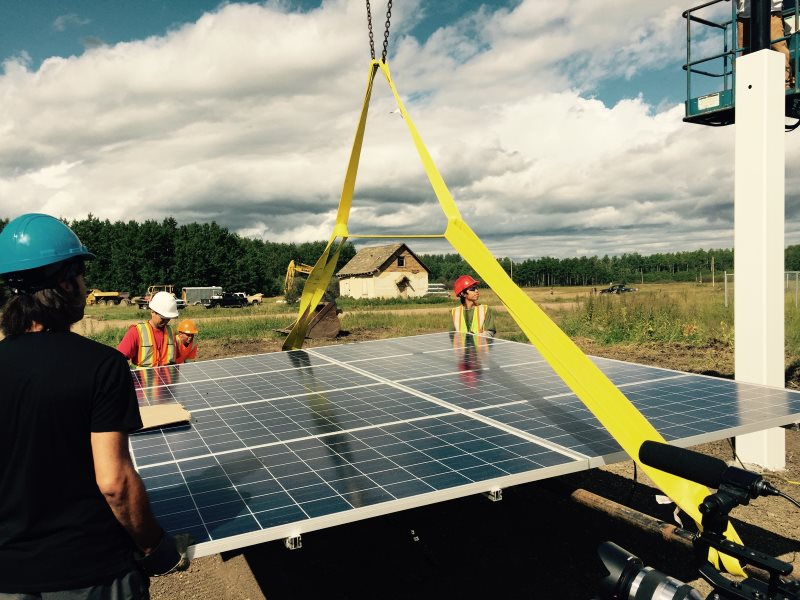 Solar panels being hoisted on to the top of pole mount solar system at Little Buffalo, Alberta.. Photo: Melina Laboucan-Massimo.
