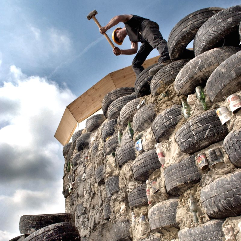 Darren Howarth building the main wall of the Brighton Earthship using waste tyres filled with earth. Photo: Roger Ba.