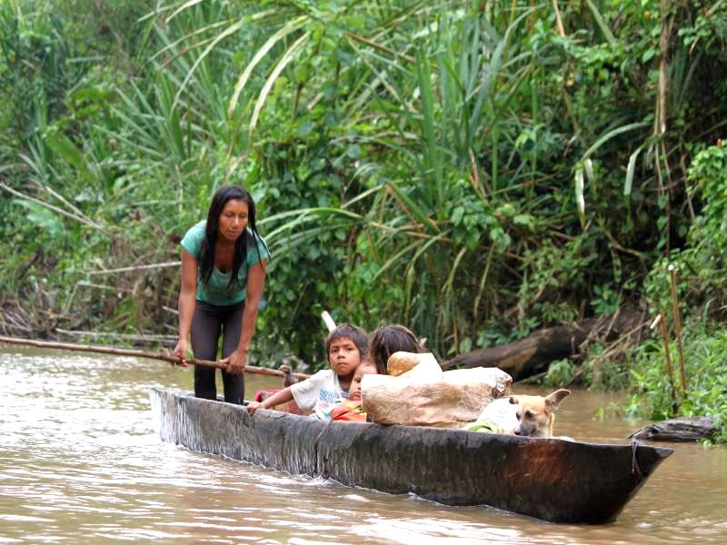 Indigenous family traveling by canoe on the Bobonaza River in the Ecuadorian Amazon. Photo: Kevin Koenig / Amazon Watch.
