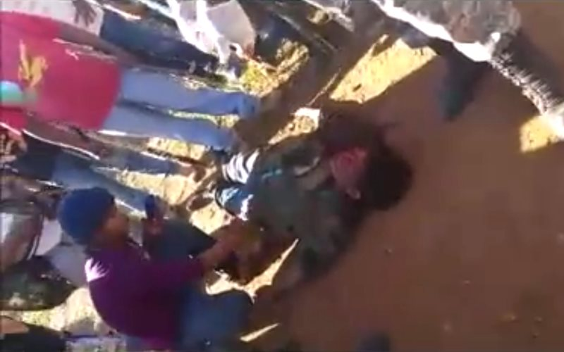 Guarani man Semião Vilhalva lies on the ground, murdered by ranchers' gunmen on 29th October 2015. Photo: still from video by Marcelo Zelic via Facebook.