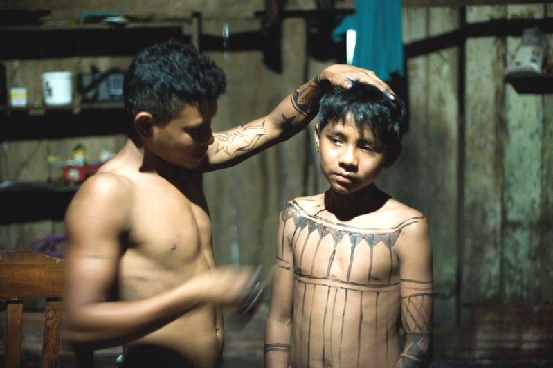 A Munduruku boy is painted with natural stain paints made from fruit. An archaeologist from the Federal University of Para, Bruna Rocha, has found ceramics on the territory dating back 1,000 years, painted with similar patterns to the ones the Munduruku u