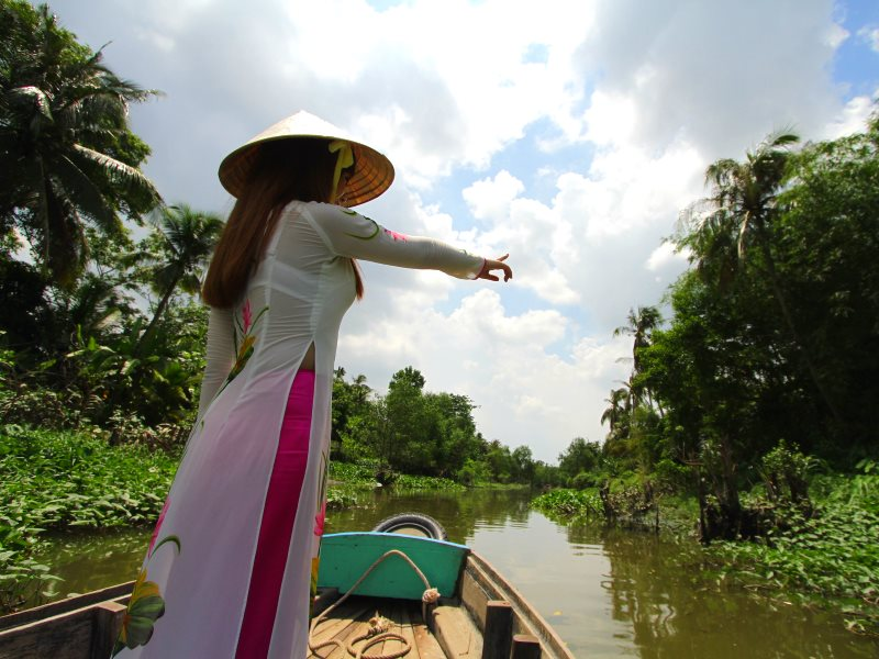 A young woman in traditional Vietnamese Ao Dai costume points toward riverside foliage. Where will this journey end? Photo: Mick Grant.