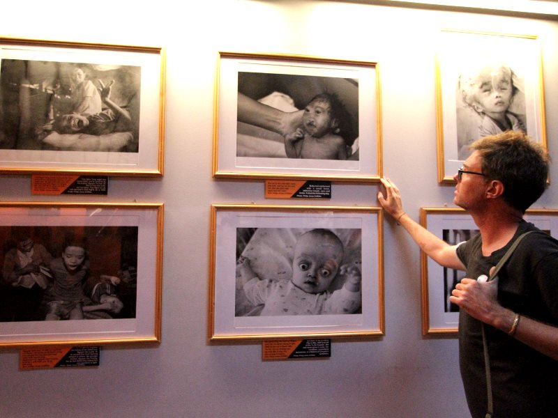Western visitor checks out Agent Orange photo-essay at the War Remnants Museum, Saigon. Photo: Mick Grant.