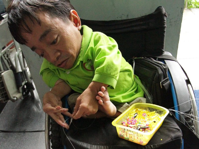A victim of congenital Agent Orange poisoning selling keychains and trinkets at the War Remnants Museum. Photo: Mick Grant.