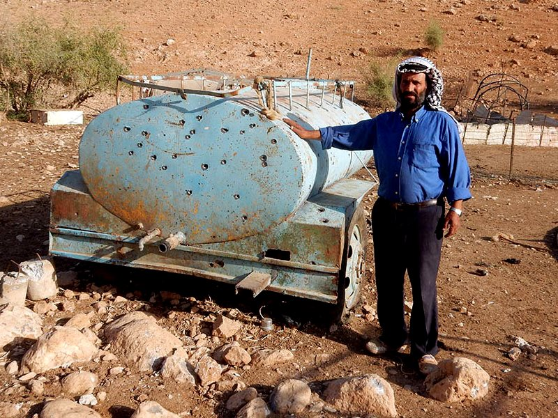 Muhammad Myadmeh by his water tank in al-Fajam after it was used by soldiers for target practice. Photo: 'Aref Daraghmeh, B'Tselem, 17 Oct. 2016.