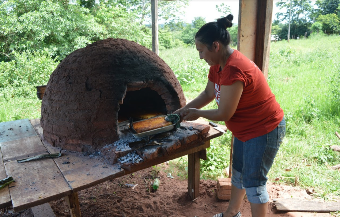 "A woman from Arsenio Vazquez removes a dish of Paraguayan soup from a ""tatakua"" (traditional clay oven), made from corn cultivated by the community. Photo by Inés Franceschelli"