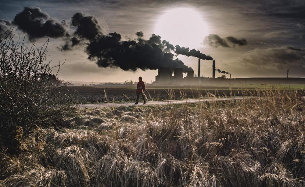 Man walking with factory in background