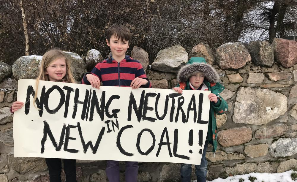 """Three chidlren hold a placard reading """"Nothing neutral in new coal"""" outside in the snow by a wall"""