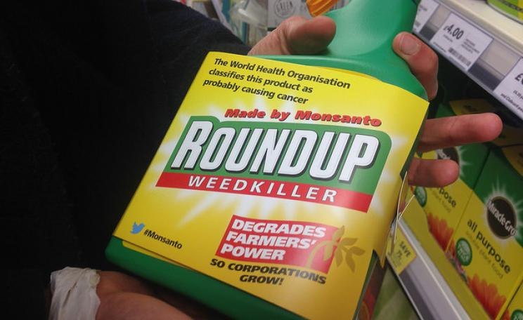 "Bottle of Roundup with added label warning, ""degrades farmers' power""."