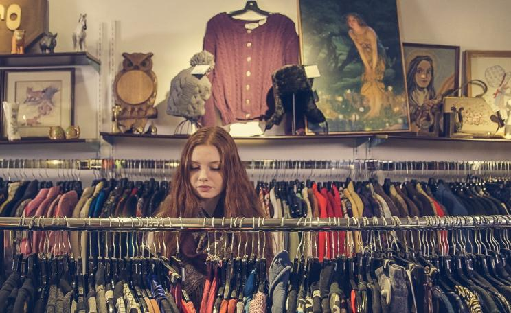 Women browses for clothes in a charity shop