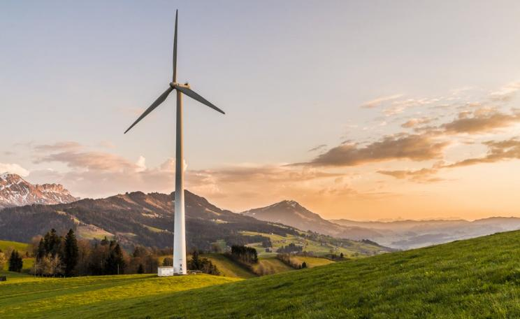 Photograph of a wind turbine at sunset