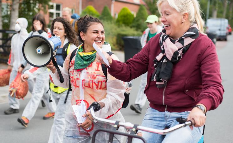 young smiling climate activist woman giving a folder to older smiling lady on a bicycle