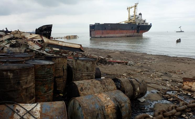 Shipbreaking yard in Bangladesh with pollution and half of a ship
