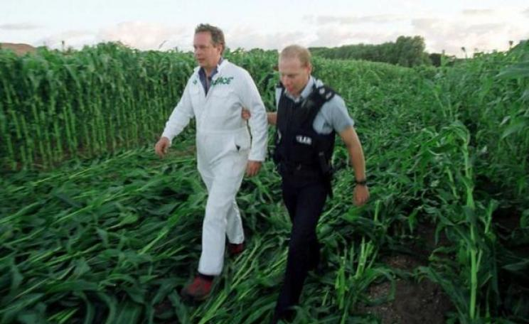 Peter Melchett being led away by a police officer at GM protest