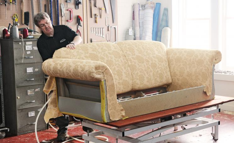 Craftsperson upholstering a sofa