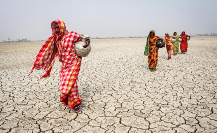 Women walking through desert in search of water