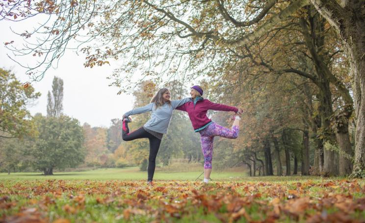 Vegans in yoga stretches in an autumn park