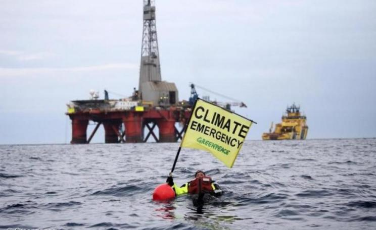"Image: Greenpeace campaigner Sarah North holds a banner reading ""Climate Emergency"" whilst floating in front of BP oil rig on day 11 of the protest in the North Sea."