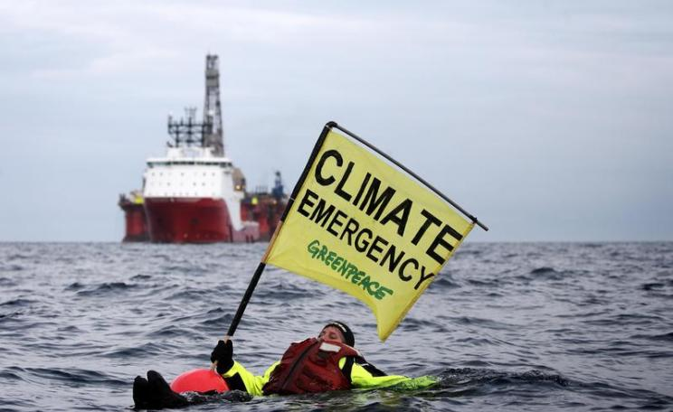 Swimmer in front of BP Oil Rig in North Sea