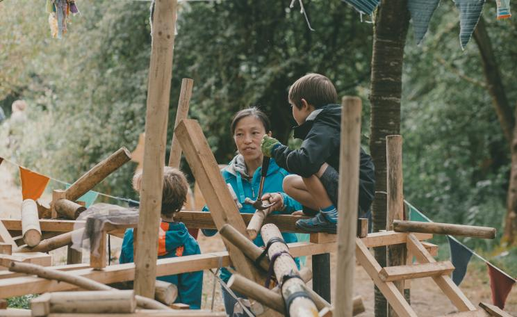 Children on a wooden playground structure that they are making themselves.