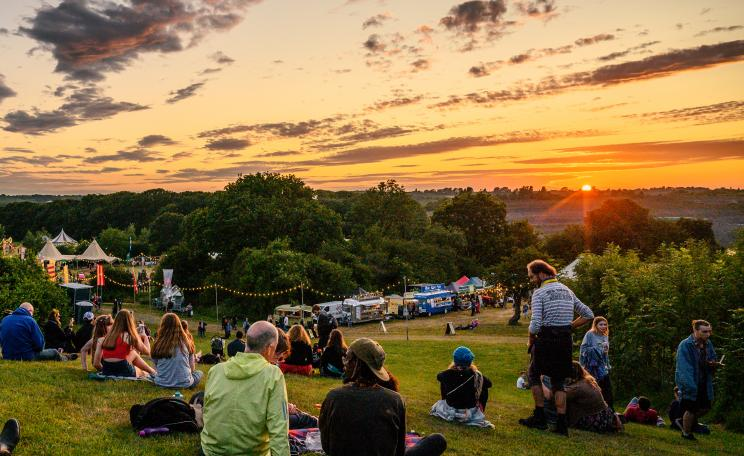 Festival audience sat on hill enjoying the sunset through the trees.