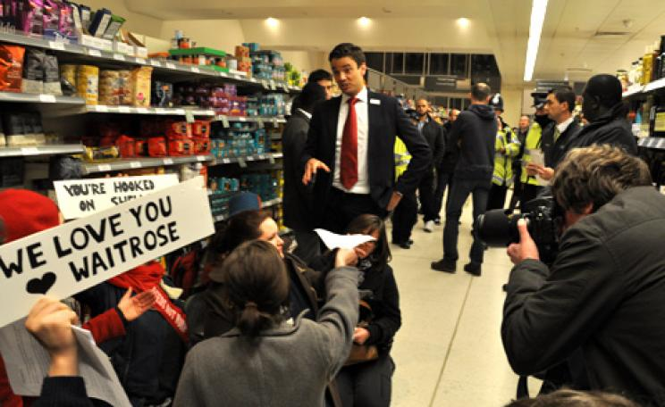 Climate Rush members protest Waitrose's relationship with Shell by occupying the store's oil aisle