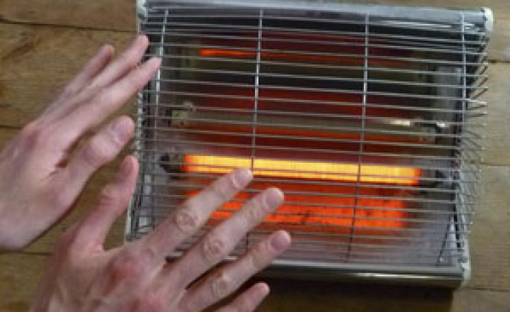 Cold hands warming on a gas heater
