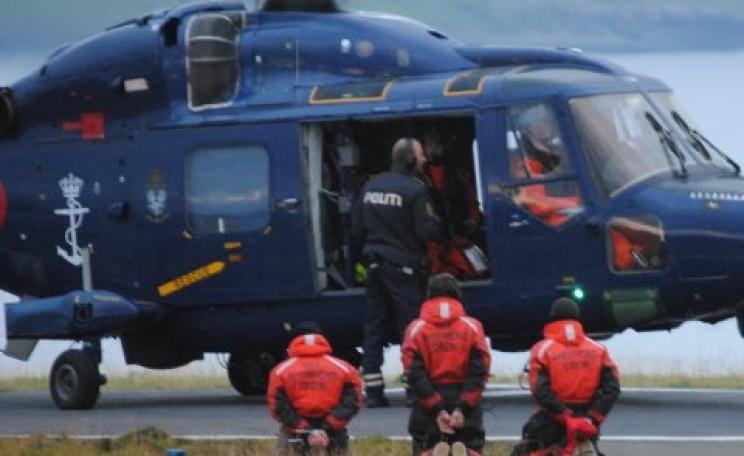 Three arrested protestors are forced to kneel before being loaded into a Danish Royal Navy helicopter. Photo: Sea Shepherd.