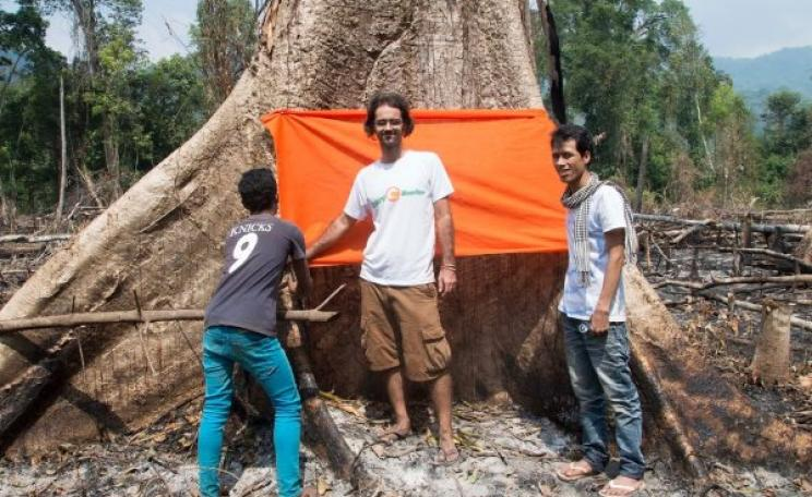 Alex standing in front of a giant tree, one of few remaining in the communal forest area at Tatai Leur in the Cardamom mountain forests. This tree blessing ceremony with villagers and Buddhist monks in 2013 sparked a wave of direct action which led to the