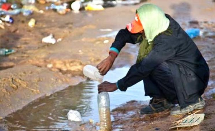 Deprived of piped water supply, a man in post-invasion Libya fills up a bottle of water from a muddy puddle. Photo: British Red Cross.