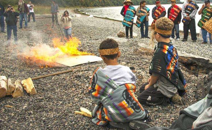 Young participants observing the flames at the symbolic check burning ceremony. Photo: Paul Anderson / EarthJustice.