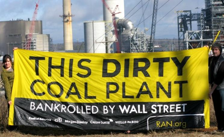 RAN activists holding a banner in front of Duke Energy's Cliffside coal plant in Cliffside, North Carolina, denouncing the banks responsible for its financing. Photo: Rainforest Action Network via Flickr (CC BY-NC).