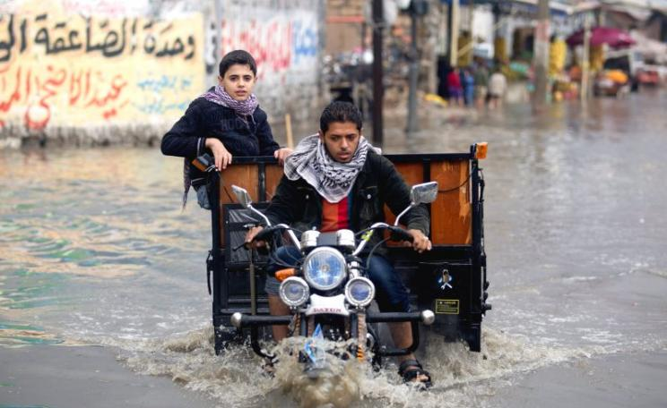 A Palestinian rides his trike through a flooded street following the heavy storms of 2013. Photo: AFP PHOTO  / MOHAMMED ABED via Flickr / Globovisión (CC BY-NC)