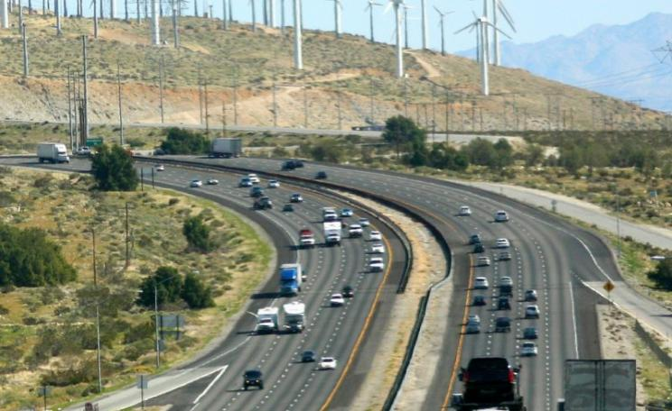 For some decades to come, old and new energy systems will have to maintain an uneasy coexistence - as at Interstate 10 near Palm Springs, California. Photo: Kevin Dooley via Flickr (CC BY).